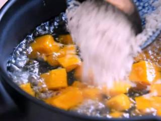 周末营养早餐—— 南瓜小米粥,再将洗净的大米倒入锅中煮2分钟