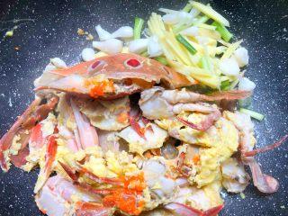 葱姜炒蟹,待蛋液凝固,翻炒均匀,把蟹块拨到一边,放入姜丝和葱白炒香