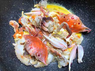 葱姜炒蟹,煎到三眼蟹壳变成红色,倒入剩下的蛋液