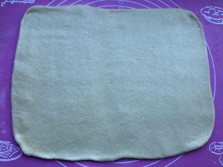 蛋黄炼乳卷,取出面团,进行排气后再冷藏松弛15分钟,接着把面团擀开成长方形面皮,宽度和烤盘差不多。