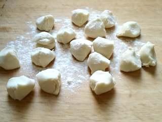 茼蒿馅饺子,饧好的面取出一块,搓成长条,揪成一个个大小适中的剂子,加干面粉防粘,搓圆,按扁。