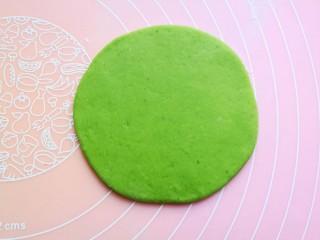 浪漫双色花馒头,取一个面团搓圆压扁,也擀薄擀成一个圆形。