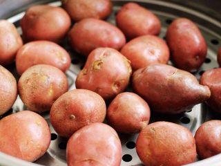 土豆火腿肠饼,蒸锅里加入适量清水、把土豆放到上面、盖上锅盖大火蒸20分钟左右即可关火