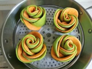 浪漫双色花馒头,锅中放入足够的水,烧至温热关火,将馒头放至蒸笼后放在锅上,盖好盖子进行第二次发酵,把馒头发酵比之前大。