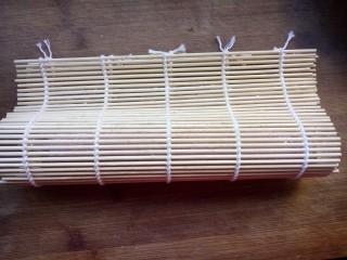 樱花寿司,拖动保鲜膜把海苔至于竹帘边缘,然后对折成水滴状,两手用力压紧。
