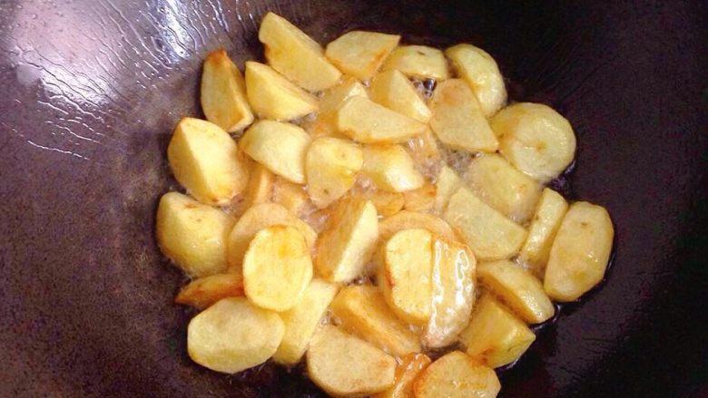 地三鲜,炒锅烧热,倒入适量食用油(跟平时炒菜的油量一样多就行),下入土豆块稍微炸至金黄边捞出。