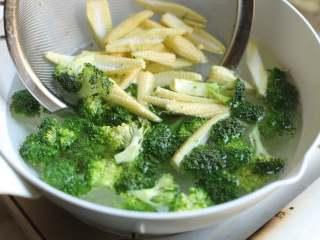 炒三脆,锅中加入清水烧开,加入些许盐和油,放入西兰花和玉米笋,焯水两分钟,然后捞出用冷水冲凉,沥去水分。