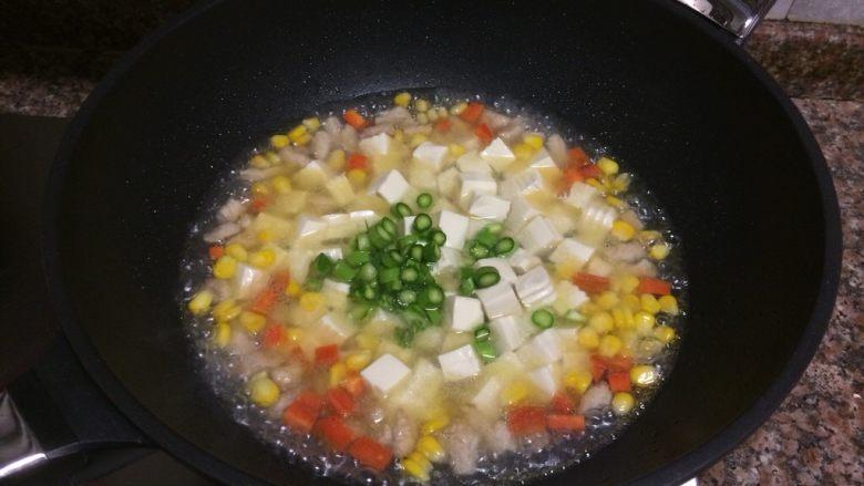 什锦豆腐羹,放入豆腐和芦笋,加入盐后煮约1-2分钟。