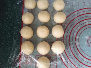 香葱火腿芝士面包,取出排气按总量分成13个份、再搓圆盖膜松驰15分钟