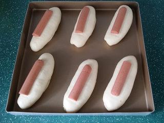 香葱火腿芝士面包,轻轻压扁后放一节香肠、再向下按一按