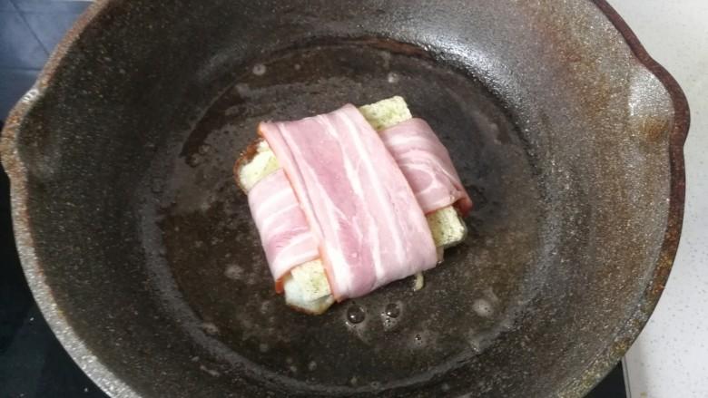 芝士培根三明治,再放入培根吐司中小火煎至两面焦黄即可
