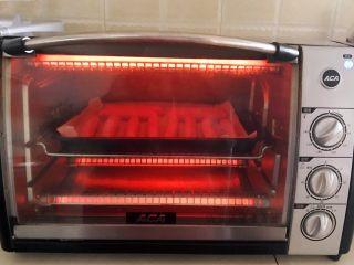 黑椒烤肠,把烤盘放入预热好的烤箱里,上下火200W,烤5分钟