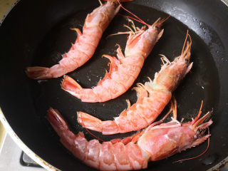 野山蒜煎大虾,平底锅里放入适量的油,油5成热时把大虾放进去,中小火煎,