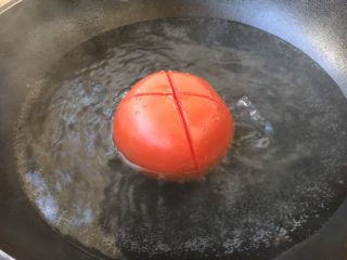 #了不起的小番茄# 番茄鲜虾蔬菜鸡蛋挂面汤(早餐),将划好十字的番茄焯烫2分钟,然后过凉水。