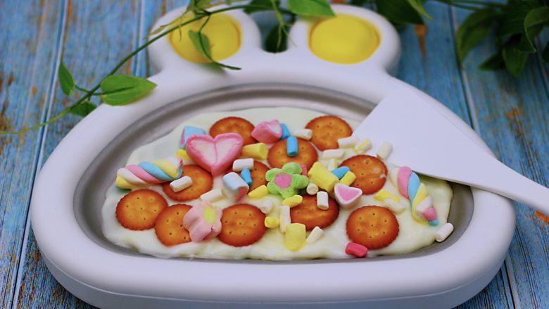饼干棉花糖炒酸奶,然后在平铺好的饼干上面。撒上适量的彩色棉花糖,不喜欢彩色的棉花糖,可以换成纯白色的哈,我是觉得酸奶本身就是白色的,所以换了彩色的棉花糖哟