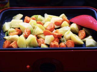三汁焖鸡翅,先爆香葱和大蒜后,加入胡萝卜块和土豆块进行翻炒片刻,一定要小火煸炒哟,大火炒容易炒糊的;