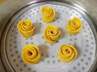 南瓜玫瑰花馒头,蒸锅内加水,铺上硅胶垫,放上做好的玫瑰花馒头生胚,盖上锅盖二次发酵10分钟左右,凉水上锅,上汽后转中火蒸18分钟关火,焖5分钟左右。