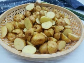 香辣小土豆,泡好的土豆轻轻搓洗干净,不喜欢吃土豆皮的,可以刮一下,因为是新土豆,用刀或者啤酒盖子轻轻一刮就没有了,我喜欢吃带皮的,所以直接对半切开就可以,切开煮的快一点,不切的话煮熟以后直接拍扁煎就可以