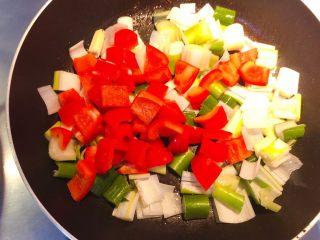红椒炒牛肉粒,加红椒粒继续翻炒。