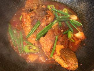 豆瓣鱼,最后汤汁变少,要起锅前放入葱段,即可盛出。