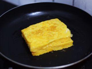 火腿西多士,平底锅刷少许食用油烧热,把沾裹蛋液的吐司放入,小火煎至金黄色