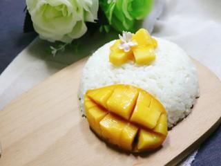 芒果糯米饭,最后把一半的芒果切花侧摆在米饭一边即可。