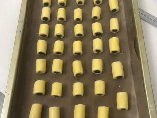 豆沙一口酥,三条全部做完排在一起切成3厘米长一段放入烤盘,表面刷上蛋黄液。