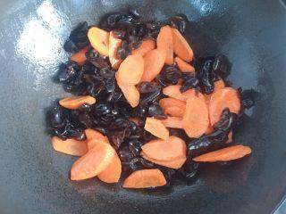 黑木耳炒肉片,再起锅倒入少许油,放入胡萝卜片、黑木耳、大火翻炒1分钟左右