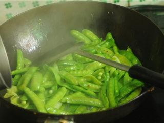 豌豆烧牛肉,锅里倒入少量的油,烧至八成热时放入豌豆片翻炒一会儿,沿着锅边淋入少许水