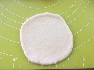 红豆包,取一份松弛好的面团,用擀面杖擀成圆片