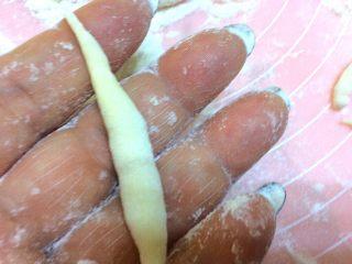 辣炒手搓土豆面鱼,取一个丁,放在手心,两手对搓,搓成两头尖,中间粗,如图