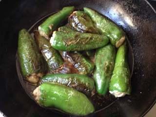 酿青椒,放入炸好的青椒盖上盖,中小火煮约8-10分钟,待汤汁收至较稠即可出锅
