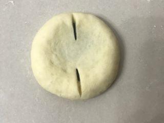 豆沙花朵面包,用手掌按扁尽量按圆一些,用割包刀割口