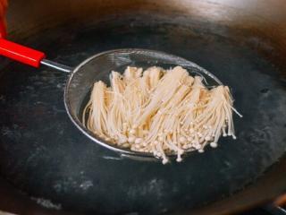 凉拌金针菇,金针菇已经变成软软的啦。捞起来,沥干,装盘。
