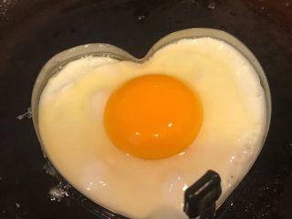 手抓饼开心早餐,锅中倒入适量底油加热摆入心形模具打入鸡蛋