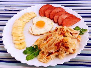 手抓饼开心早餐,煎好的手抓饼、鸡蛋、火腿还有切好的香蕉摆入盘中