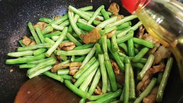 五花肉煸豆角,加入少许生抽,盖锅盖焖煮片刻。