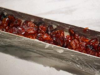 蔓越莓糯米糕,保鲜膜上最好轻轻摸一层黄油或者无异味的油,便于脱模,用手取一团捣烂的糯米均匀的铺在模具内压平,然后再铺上准备好的蔓越莓干