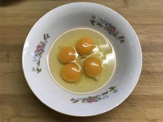 蚕豆炒鸡蛋,四个鸡蛋打入碗中。