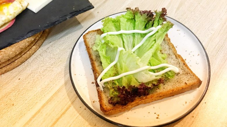 巨无霸早餐三明治😋,吐司片上放两片<a style='color:red;display:inline-block;' href='/shicai/ 121'>生菜</a>挤沙拉酱。