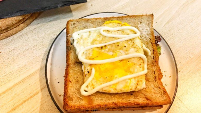 巨无霸早餐三明治😋,盖上一层面包片,放上糖心蛋,挤上沙拉酱。