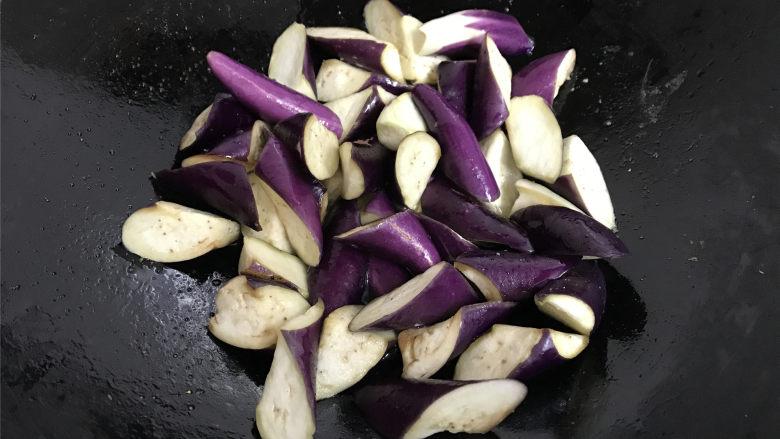 地三鲜,锅中倒入适量油先把腌好的茄子放入炸至茄子边缘呈透明色后捞出。