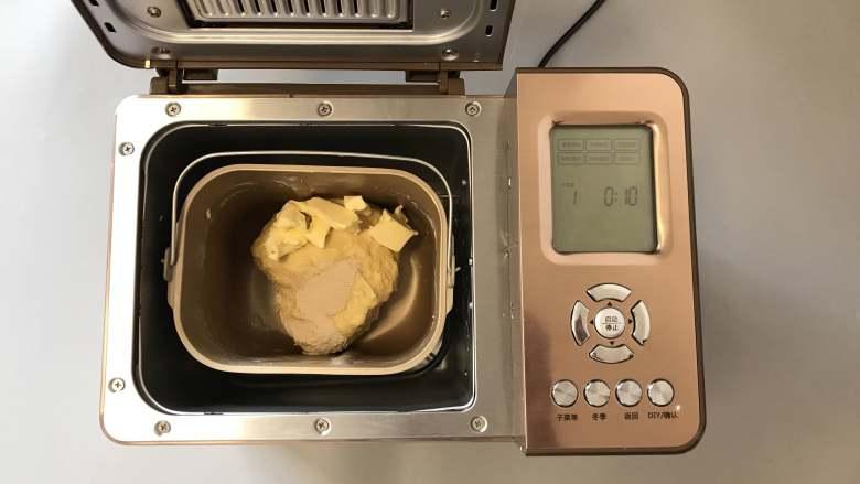 面包机版咕咕霍夫面包,10分钟后加入<a style='color:red;display:inline-block;' href='/shicai/ 731'>酵母</a>以及第二份1/3黄油,继续启动和面10分钟。