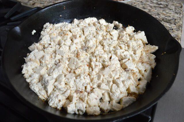 鸡肉蔬菜杯,锅里加一勺油。加入豆腐。把火调高,把豆腐捣碎。直到水分都蒸发,豆腐开始变色, 一定要不停搅拌一下 。