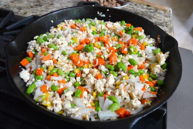 鸡肉蔬菜杯,加入胡萝卜、玉米、毛豆和洋葱。把所有的东西一起搅拌,炒制2分钟。