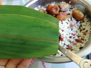 杂豆蜜枣粽,粽叶需要刷子洗几次,开水烫一下,洗粽叶的过程我就没拍图了,估计大家都懂的,然后取一大一小两片粽叶,大的在下面,小的在上面,剪去头。