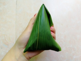 杂豆蜜枣粽,然后再把粽叶折回来收口,粽叶太长的话,可以剪掉一些