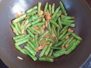干煸四季豆,翻炒均匀后继续铺平,直到四季豆像图片里这种程度即可出锅了