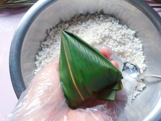 蜜枣西米粽子,顺着边边将粽叶折好;