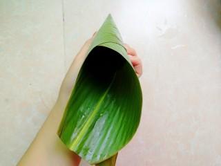 杂豆蜜枣小米粽,然后手捏住上面那一头粽叶转一圈,形成更长的牛角形状,看不懂的多看上图和此图的区别,就明白了